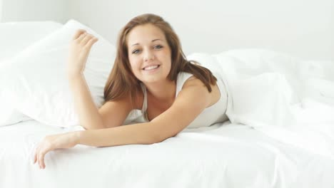 Young-Woman-Relaxing-In-Bed-Smiling-And-Laughing-At-Camera