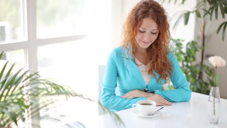 Young-Woman-Siting-At-Table-Holding-Cup-Of-Coffee-And-Smiling