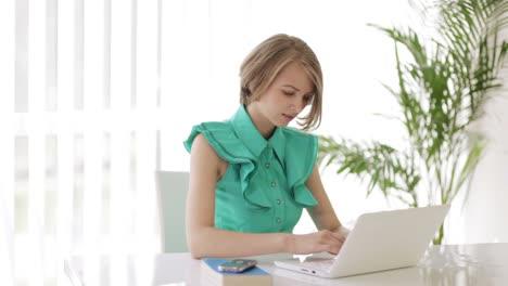 Mujer-Joven-Sentada-En-El-Escritorio-Usando-Laptop-Mirando-A-La-Cámara-Y-Sonriendo-Panorámica