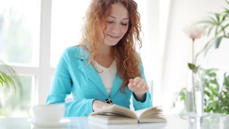 Young-Woman-Sitting-At-Table-Drinking-Coffee-Reading-Book-And-Smiling