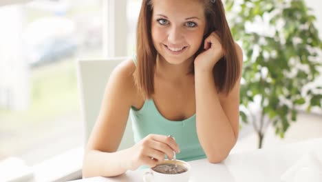Young-Woman-Sitting-At-Table-Stirring-Coffee-Looking-At-Camera-Smiling-And-La