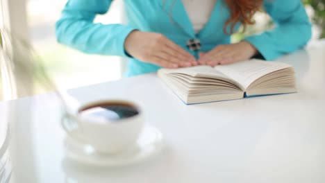 Young-Woman-Sitting-At-Table-With-Book-And-Cup-Of-Coffee