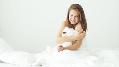 Junge-Frau-Sitzt-Auf-Dem-Bett-Und-Umarmt-Den-Teddybär-Der-Gähnt-Und-In-Die-Kamera-Lächelt