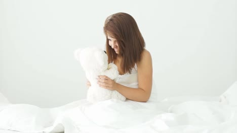Young-Woman-Sitting-On-Bed-Playing-With-Teddy-Bear-And-Smiling-At-Camera