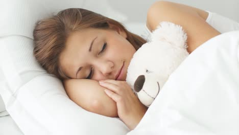 Young-Woman-Sleeping-In-Bed-Hugging-Teddy-Bear-Moving-And-Smiling-In-Sleep