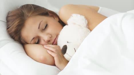 Young-Woman-Sleeping-In-Bed-Hugging-Teddy-Bear-Smiling-In-Sleep