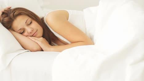 Joven-Mujer-Durmiendo-En-La-Cama-Despertando-Y-Sonriendo-A-La-Cámara-01