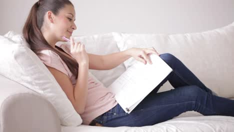 Attractive-Student-Girl-Sitting-On-Sofa-Writing-In-Student-s-Book-And-Smiling
