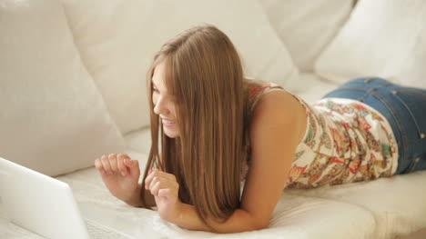 Beautiful-Girl-Lying-On-Sofa-Using-Laptop-And-Smiling