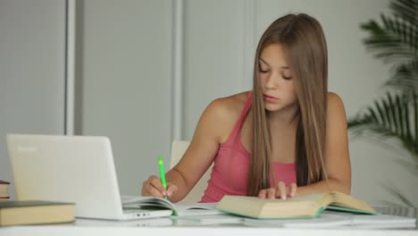 Beautiful-Girl-Studying-At-Table-And-Smiling-At-Camera