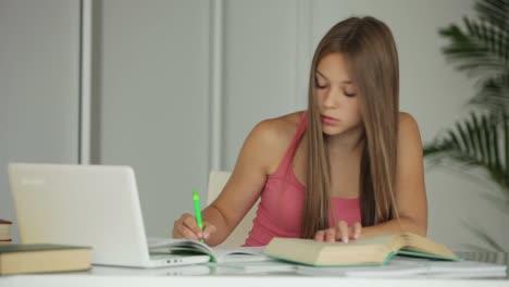Hermosa-Chica-Estudiando-En-La-Mesa-Y-Sonriendo-A-La-Cámara