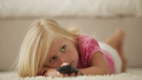 Beautiful-Little-Girl-Lying-On-Carpet-Using-Remote-Control-And-Smiling