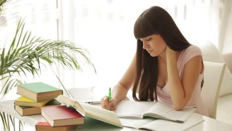 Hermosa-Chica-Estudiante-Sentada-En-La-Mesa-Estudiando-Y-Escribiendo-En-El-Cuaderno