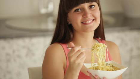 Charming-Girl-At-Kitchen-Eating-Noodle-And-Smiling