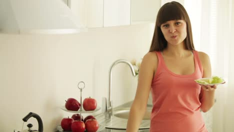 Charming-Girl-In-Kitchen-Eating-Fruits-And-Smiling-At-Camera