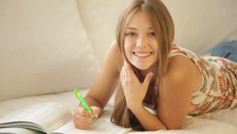 Charming-Girl-Lying-On-Sofa-Writing-In-Notebook-And-Smiling
