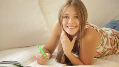 Encantadora-Niña-Acostada-En-El-Sofá-Escribiendo-En-El-Cuaderno-Y-Sonriendo