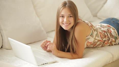 Chica-Encantadora-Descansando-En-El-Sofá-Usando-Laptop-Y-Sonriendo