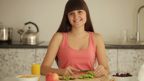 Charming-Girl-Sitting-At-Kitchen-Table-And-Slicing-Kiwi