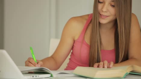 Charming-Girl-Sitting-At-Table-And-Writing-In-Notebook-01