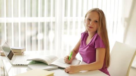 Encantadora-Niña-Sentada-A-La-Mesa-Con-Libros-Y-Laptop-Escribiendo-En-El-Libro-De-Trabajo-Buscando-01