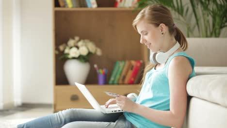 Charming-Girl-Sitting-On-Carpet-Using-Laptop-Holding-Credit-Card