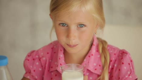 Charming-Little-Girl-Drinking-Milk-And-Smiling-At-Camera