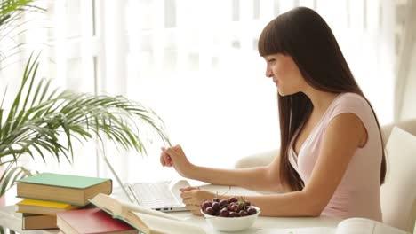 Encantadora-Chica-Estudiante-Sentada-En-La-Mesa-Usando-Una-Computadora-Portátil-Y-Comiendo-Cerezas