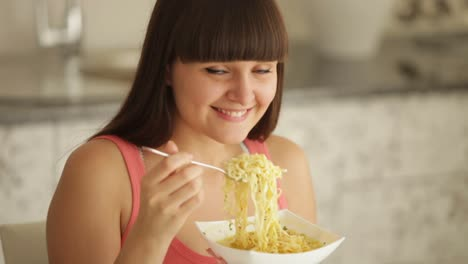 Cheerful-Girl-At-Kitchen-Eating-Noodle-And-Smiling