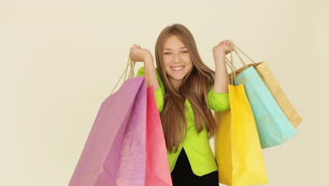 Cheerful-Girl-Holding-Shopping-Bags-And-Smiling