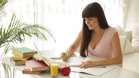 Alegre-Niña-Sentada-En-La-Mesa-Y-Estudiando-Con-Libros-Y-Laptop