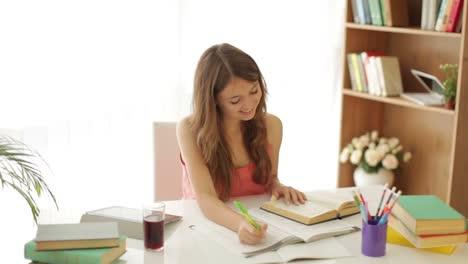 Alegre-Niña-Sentada-En-La-Mesa-Estudiando-Escribir-En-El-Libro-Mirando-La-Cámara