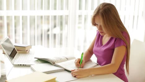 Cheerful-Girl-Sitting-At-Table-With-Books-And-Laptop-Writing-In-Workbook-Looking