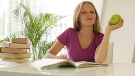 Alegre-Niña-Sentada-En-La-Mesa-Escribiendo-En-El-Cuaderno-Agarrando-Manzana