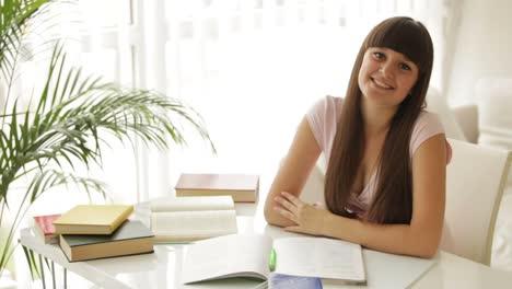 Chica-Alegre-Estudiando-En-La-Mesa-Con-Libros-Escribiendo-En-El-Cuaderno-Y-Sonriendo-A