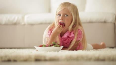 Cheerful-Little-Girl-Lying-On-Floor-And-Eating-Strawberries