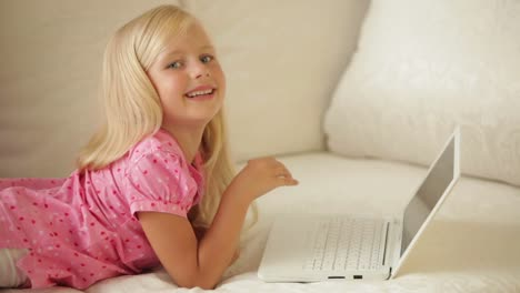 Cheerful-Little-Girl-Lying-On-Sofa-Using-Laptop-And-Smiling