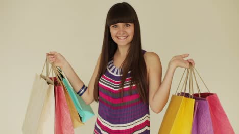 Cute-Girl-Holding-Shopping-Bags-And-Smiling