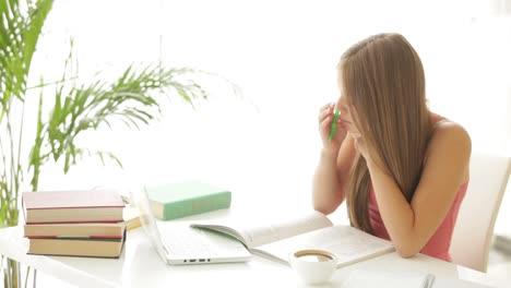 Linda-Chica-Sentada-En-La-Mesa-Y-Estudiando-Con-Libros-Y-Laptop