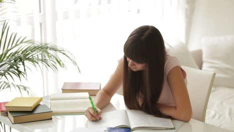 Linda-Chica-Sentada-En-La-Mesa-Estudiando-Y-Escribiendo-En-El-Cuaderno