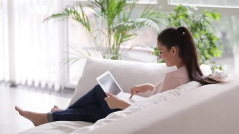 Linda-Chica-Sentada-En-El-Sofá-Con-Laptop-Mirando-A-Cámara-Y-Sonriendo