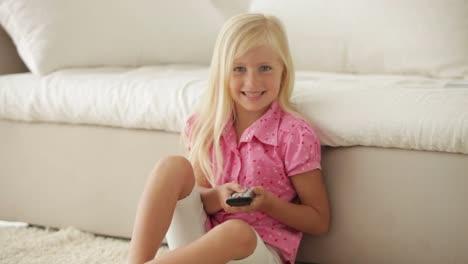 Süßes-Kleines-Mädchen-Das-Auf-Dem-Boden-Sitzt-Und-Knöpfe-Auf-Der-Fernbedienung-Drückt-Pushing