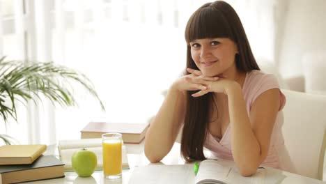 Linda-Chica-Estudiante-Sentada-En-La-Mesa-Estudiando-Y-Sonriendo-A-La-Cámara