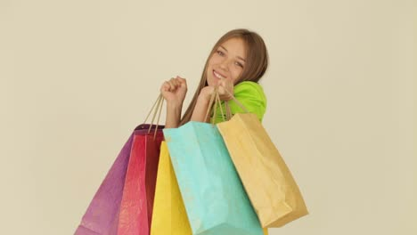 Excited-Girl-Holding-Shopping-Bags-And-Smiling