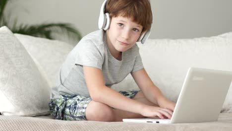 Funny-Boy-In-Headset-Sitting-On-Sofa-And-Using-Laptop