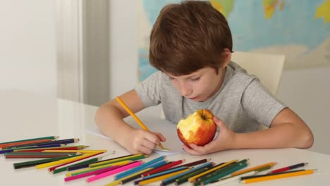 Funny-Little-Boy-Sitting-At-Desk-Eating-Apple-And-Drawing