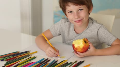 Funny-Little-Boy-Sitting-At-Table-And-Drawing-With-Colored-Pencils