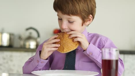 Funny-Little-Boy-Sitting-At-Table-And-Eating-Burger