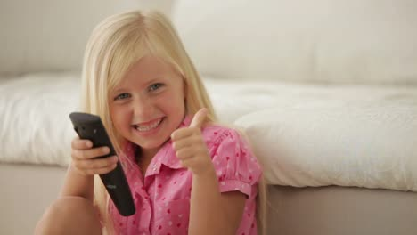 Funny-Little-Girl-Holding-Remote-Control-Smiling-And-Showing-Thumb-Up