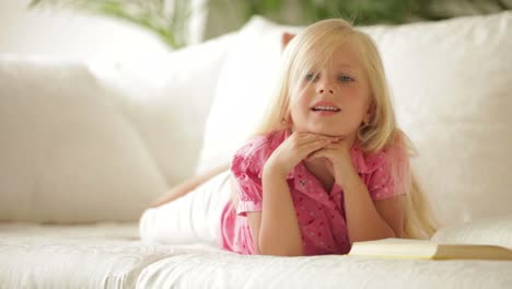 Funny-Little-Girl-Lying-On-Couch-With-Book-And-Smiling